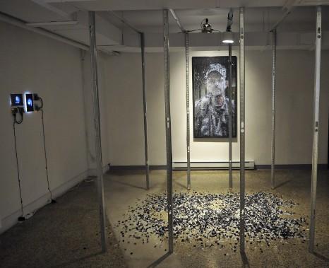 Paolo Almario propose une oeuvre lourde de sens. Le père de l'artiste est emprisonné injustement en Colombie depuis des années. Les poteaux installés rappellent justement la prison où il est enfermé. Le portrait intitulé <em>Oscar</em>, est composé de photos. Le portrait a été déconstruit dans le cadre d'une installation présentée à l'UQAC en 2014. Il a été reconstruit, mais des photos ont été perdues dans le processus. Ce sont ces... (Photo Le Progrès-dimanche, Rocket Lavoie)
