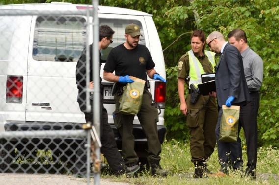 Cette photo prise mardi en fin d'après-midi montre des membres de la SQ avec des sacs contenant possiblement des preuves. (Photo: Francois Gervais)