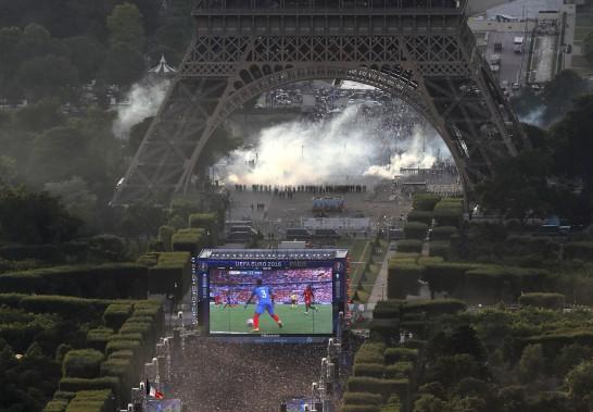 Pendant que les partisans regardent le match de l'Euro sur écran géant, un autre affrontement se déroule derrière l'écran, entre des partisans et les policiers. (AFP)