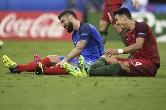 Olivier Giroud de l'équipde de France le défenseur portugais Fonte partagent un cmoment de complicité sur le terrain du Stade de France. (AFP)