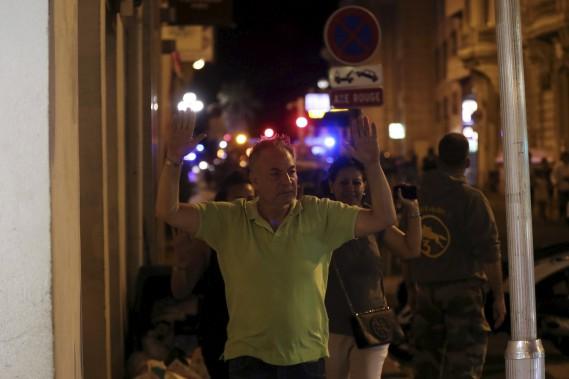 Des citoyens lèvent les bras en l'air en s'éloignant des lieux du drame. (AFP, Valery Hache)
