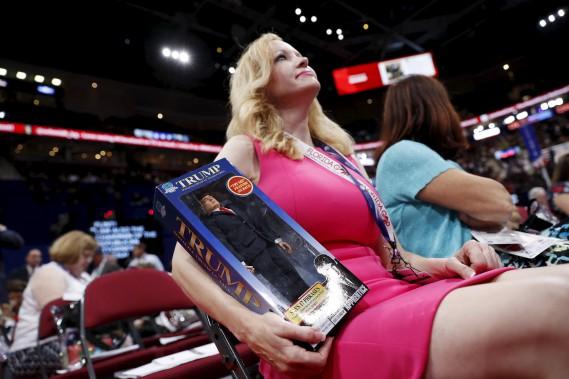 Une femme tient une figurine de Trump avant l'arrivée de ce dernier. (AP)