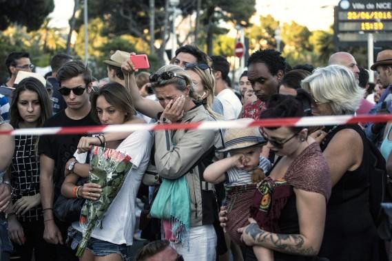 Au lendemain de l'attentat ayant fait 84 morts sur la Promenade des Anglais, à Nice, des Français se recueillent en mémoire des victimes, le 15 juillet. (PHOTO Laurent Cipriani, AP)