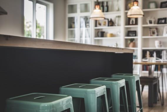 Coup d'oeil rétro-industriel de la cuisine qui s'ouvre sur la salle à manger. Du blanc, du noir, du bois et une touche de menthe! (Photographie Atypic)