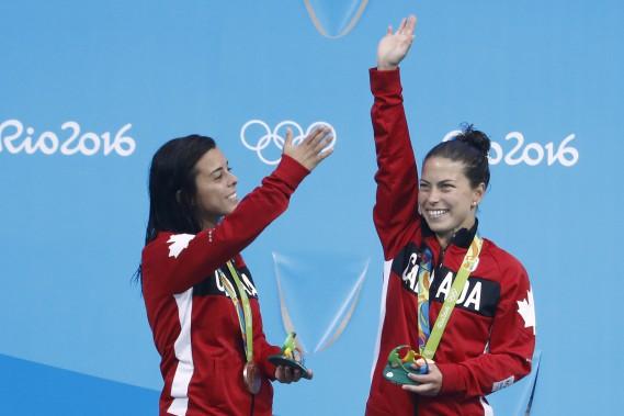 Meaghan Benfeito et Roseline Filion saluent la foule sur le podium. (Photo Odd Andersen, AFP)