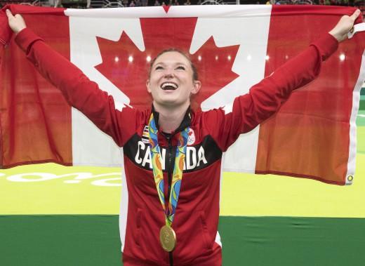 Rosie MacLennan célèbre avec le drapeau canadien après avoir remporté la médaille d'or au trampoline. (Photo Ryan Remiorz, PC)