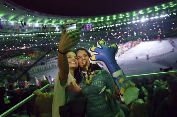 Des spectateurs posent pour un égoportrait lors de la cérémonie de clôture des Jeux de Rio. (AFP, Ed JONES)