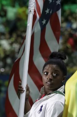 La gymnaste Simone Biles, qui a remporté cinq médailles à Rio, dont quatre d'or, porte le drapeau américain. (AP, David Goldman)