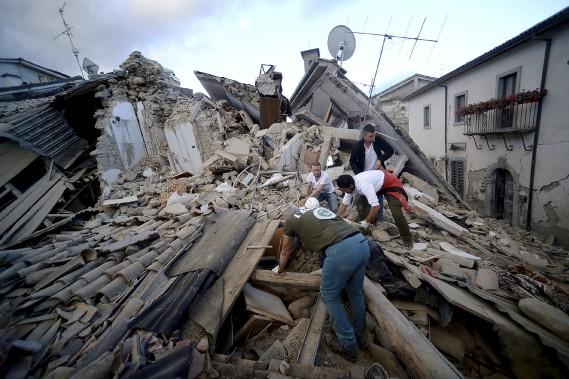 Des résidents d'Amatrice cherchent des victimes dans les décombres après un séisme de 6 qui a fait au moins 247 morts. (AFP, Filippo Monteforte)