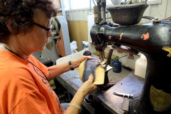 Gisèle Morin coud la semelle d'un mocassin. La machine dont elle se sert date de la fondation de l'usine et le fil utilisé doit passer dans la graisse pour ne pas brûler, tellement il est cousu rapidement. (Le Soleil, Erick Labbé)