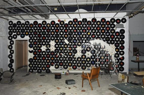 Cette salle était dans la noirceur totale à notre arrivée. C'est grâce au flash de l'appareil photo qu'on peut voir les disques sur le mur qui servaient de décoration pour le studio. Le projet initial était de loger les musiciens au sous-sol. (Photo Le Quotidien, Rocket Lavoie)