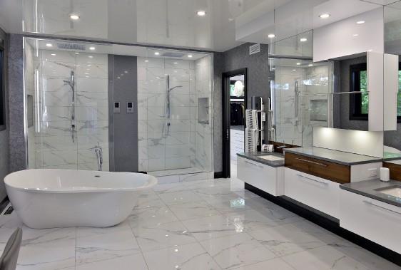 La salle de bain de la suite principale. La baignoire autoportante repose sur une céramique à effet marbre, reprise dans la douche double. Laque blanche, noyer et papier peint ton sur ton complètent ce décor volontairement épuré. - (Le Soleil, Patrice Laroche)
