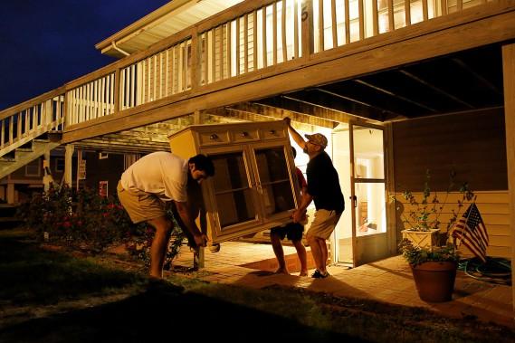 Ces hommes aident leurs proches à vider leur maison qui est sur le bord de la plage, à  Garden City Beach, dans la Caroline du Sud. (Randall Hill, REUTERS)