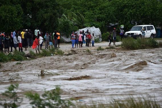 Des habitants de Cité Soleil regardent ce qui a l'apparence d'une rivière, mais qui est en fait une route. Des milliers de personnes ont dû trouver refuge à cause de <em>Matthew.</em> (AFP)
