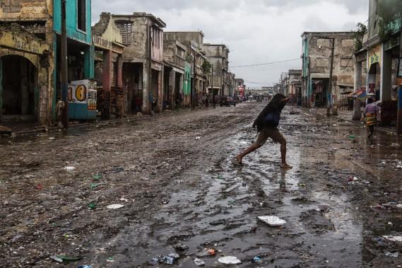 Une femme traverse une rue boueuse de Port-au-Prince. (Photo Logan ABASSI, Agence France-Presse/UNICEF)