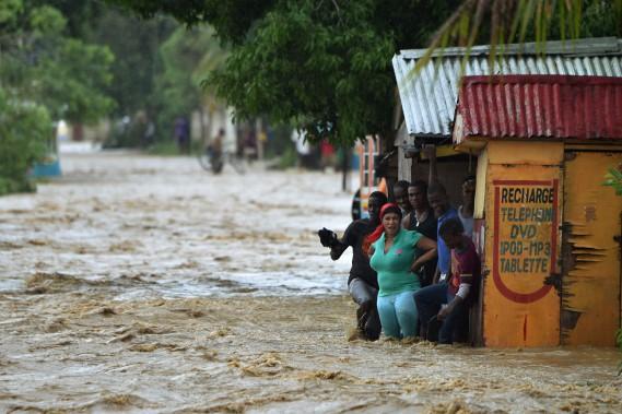 Des gens veulent traverser une rue inondée par le débordement de la rivière La Rouyonne à Leogane. (PHOTO HECTOR RETAMAL, AGENCE FRANCE-PRESSE)