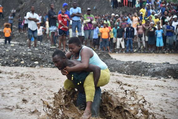 Un homme transporte une femme sur son dos pour traverser une rivière à Petit Goave. (PHOTO HECTOR RETAMAL, AGENCE FRANCE-PRESSE)