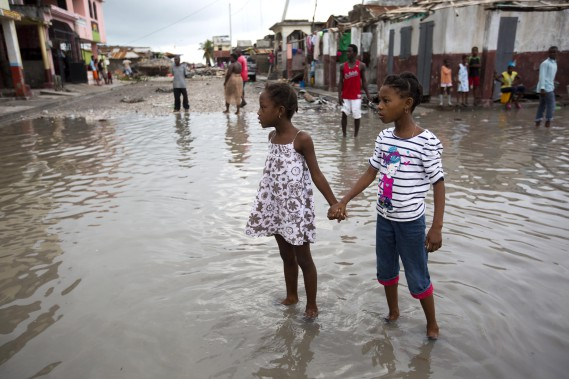 Deux enfants sur une rue inondée aux Cayes. (Photo Dieu Nalio Chery, Associated Press)