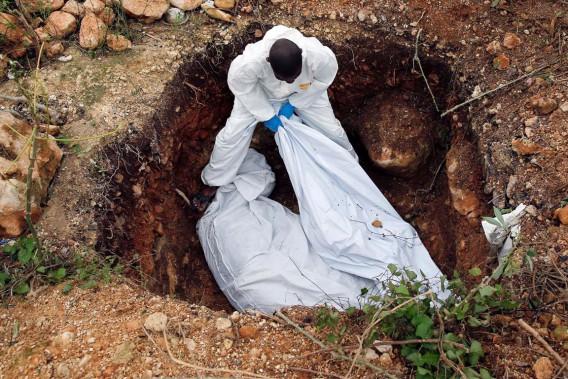 Des secouristes enterrent les corps de deux victimes de l'ouragan <em>Matthew</em> à Jérémie, le 6 octobre. La tempête a fait des centaines de morts en Haïti. (photo Carlos Garcia Rawlins, REUTERS)