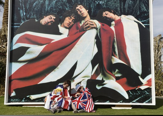 Des festivalières japonaises prennent la pose devant une grande affiche de l'album <em>The Kids Are Alright</em> de The Who. (AP, Chris Pizzello)