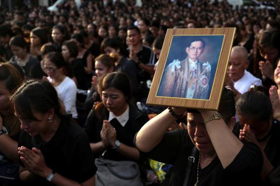 Des admirateurs du roi Bhumibol prient, une femme tenant contre sa tête un portrait du souverain qui était considéré comme un véritable père pour plusieurs Thaïlandais, alors que sa dépouille est transportée de l'hôpital où il est décédé au Grand Palais, à Bangkok, le 14 octobre. (photo Athit Perawongmetha, REUTERS)