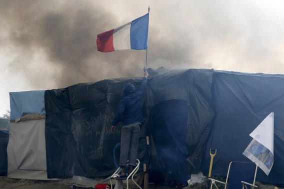 Un migrant ajuste un drapeau français sur le toit d'un abri de fortune. La jungle de Calais qui a commencé à «pousser» au début des années 2000, mais qui a pris l'ampleur qu'on lui connaissait avant son démantèlement de cette semaine avec le début de la crise migratoire en 2010, était un symbole d'échec pour plusieurs en France et en Europe. Un véritable bidonville au coeur de l'Hexagone. (photo Pascal Rossignol, REUTERS)