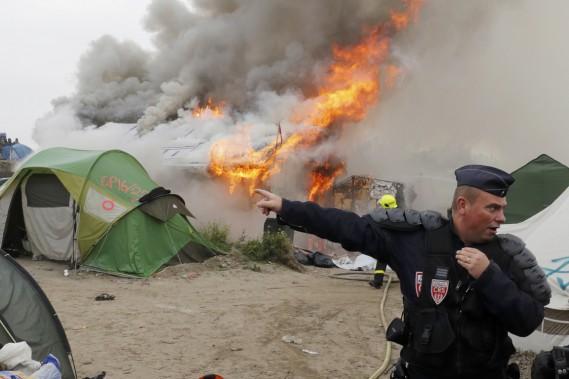 Un CRS tente de sécuriser le lieu de l'incendie. (photo Philippe Wojazer, REUTERS)