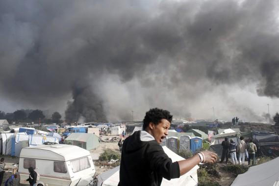 La fumée noire enveloppe la jungle, alors qu'un migrant réagit à la scène de désolation. (photo Thibault Camus, AP)