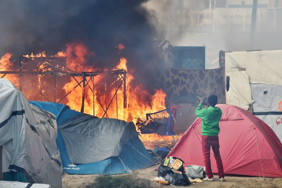 Un migrant photographie le camp qui brûle à l'aide de son téléphone intelligent. (photo  PHILIPPE HUGUEN, AFP)