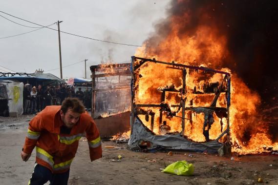 Un travailleur faisant partie de l'équipe de démolition dépêchée dans le camp pour le démanteler court se mettre à l'abri, alors que les flammes se propagent. (photo PHILIPPE HUGUEN, AFP)