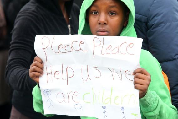Un jeune réfugié de Calais tente d'interpeller intervenants, policiers et journalistes en brandissant une pancarte où l'on peut lire en anglais: «S'il vous plaît aidez-nous, nous sommes des enfants». (photo François NASCIMBENI, AFP)