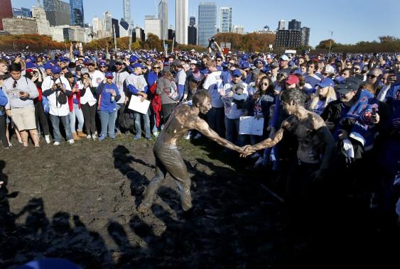 Ces deux partisans des Cubs se serrent la main après avoir fait de la lutte dans la boue, à Grant Park. (Photo Charles Rex Arbogast, AP)