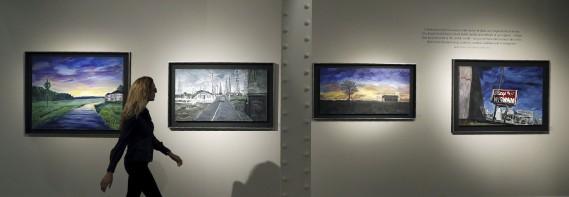 Un employé de la galerie d'art Halcyon, la veille de l'inauguration de l'exposition du prolifique peintre et lauréat du Nobel de littérature. (AFP, Adrian Dennis)