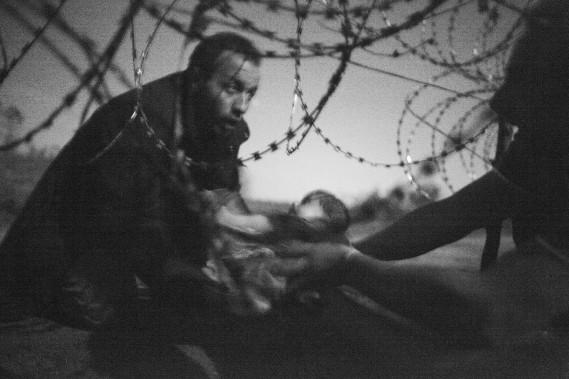 Un homme qui passe un bébé sous des fils barbelés à la frontière entre la Serbie et la Hongrie a valu le titre de Photo de l'année à Warren Richardson de l'Australie. (Photo courtoisie, Warren Richardso)