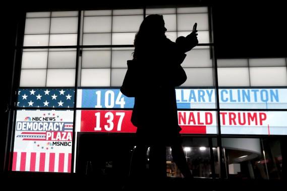 Une femme marche devant un panneau d'affichage présentant les résultats au Rockefeller Center, à New York. (AP)