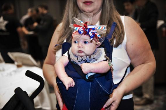 Une fillette portée par sa mère observe une salle remplie de supporters républicains à Dallas, au Texas. (Photo Laura BUCKMAN, AFP)