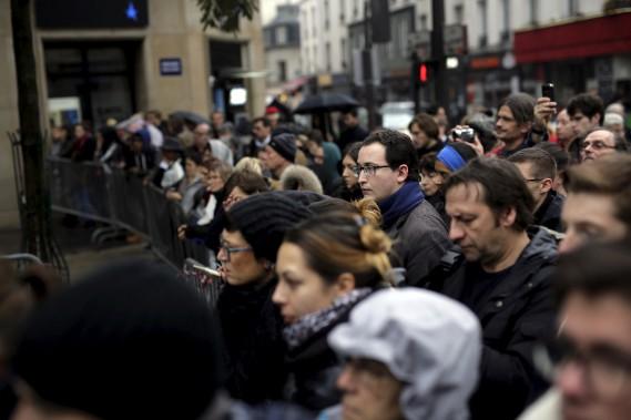 Des gens se sont rassemblés devant le Bataclan dimanche afin de commémorer la mémoire des disparus. (AP, Jerome Delay)