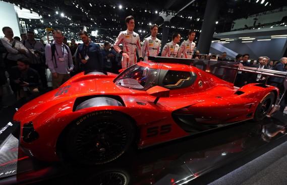 Les coureurs de l'écurie Mazda posent à côté de la voiture de courseMazda RT24-P DPi. (E)