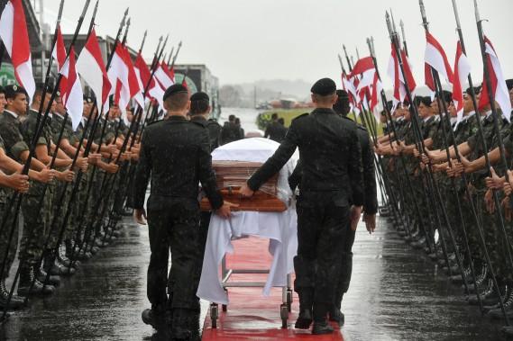 Des militaires transportent les cercueils des joueurs de soccer tués dans l'écrasement d'avion. (AFP)
