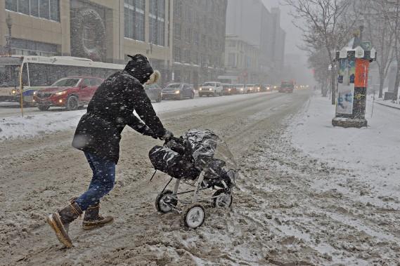 Une femme traverse la rue de peine et de misère avec sa pousette au centre-ville de Québec. (Le Soleil, Patrice Laroche)