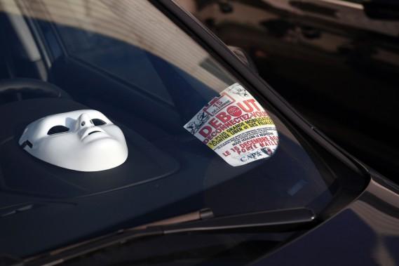 Un masque blanc et un tract enjoignant les chauffeurs à se déconnecter d'Uber sont mis en évidence dans une voiture lors d'une manif à Paris. (AFP)