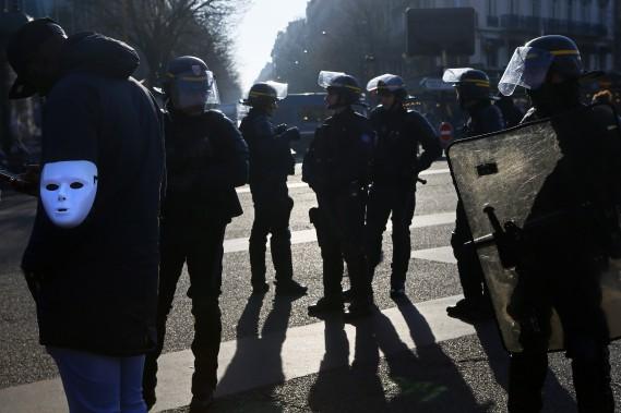 Un manifestant anti-Uber portant un masque au bras, non loin de policiers anti-émeute, a participé avec des centaines d'autres chauffeurs au blocage de la Porte Maillot, à Paris.<br /><br /> (AP)
