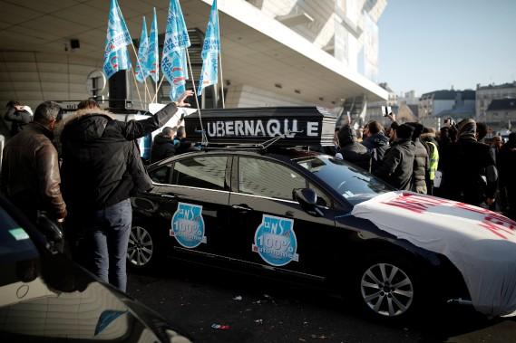 Un faux cercueil portant l'inscription Ubernaque, attaché sur le toit d'une voiture, lors d'une manifestation de chauffeurs dénonçant comme une arnaque les conditions de travail d'Uber. (REUTERS)