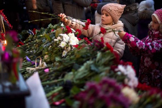 Deux fillettes déposent des fleurs au mémorial érigéà l'extérieur de la salle de spectacle des choeurs de l'Armée rougeà Moscou. (PHOTO AFP)