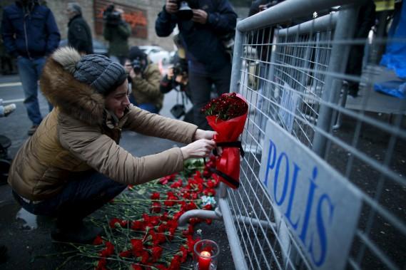Des gens sont venus déposer des fleurs devant le bar Reina au lendemain des tragiques événements. (AP, Emrah Gurel)