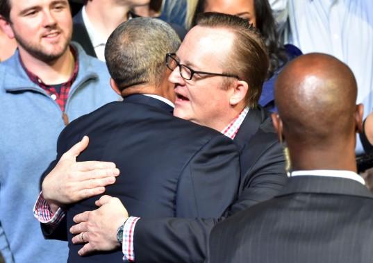 Obama enlace l'ancien porte-parole de la Maison Blanche Robert Gibbs, qui assistait à son discours. (AFP)