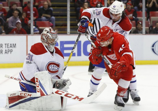 Carey Price repousse un lancer alors que Mark Barberio (45) tente d'empêcher Luke Glendening (41) de s'emparer d'un retour. (Photo Paul Sancya, AP)