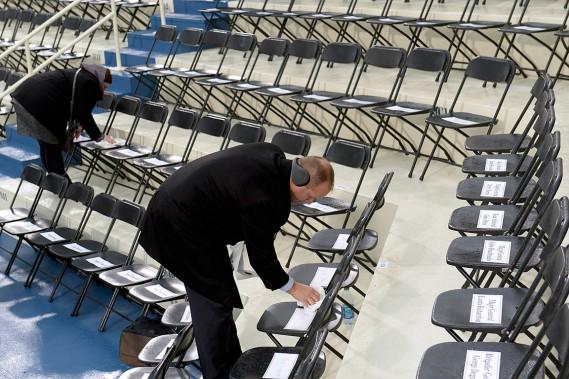 Deux travailleurs essuient les sièges destinés aux invités d'honneur. (Photo Saul Loeb, REUTERS)