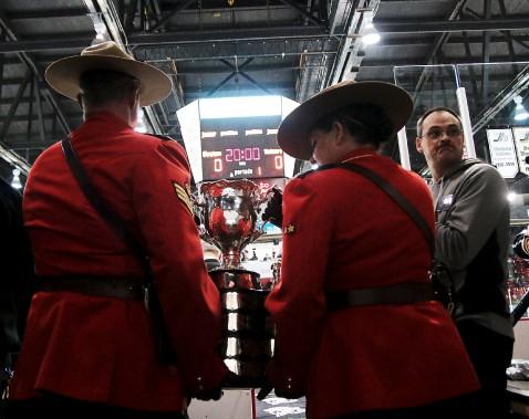 Des membres de la Gendarmerie royale du Canada transportent le précieux trophée sur la patinoire. (Etienne Ranger, Le Droit)
