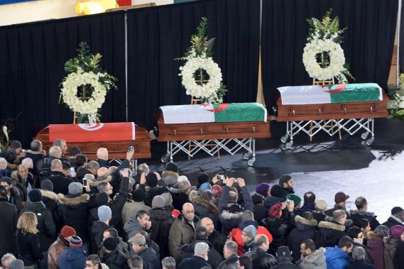 Dans un coin de la patinoire, recouverte d'un plancher de bois noir pour l'occasion, trois cercueils étaient alignés. Le drapeau d'Algérie recouvrait ceux de Khaled Belkacemi, 60 ans, professeur au Département des sols et de génie agroalimentaire de l'Université Laval, et d'Abdelkrim Hassane, 41 ans, analyste programmeur au Centre de services partagés du Québec. Le cercueil d'Aboubaker Thabti, 44 ans, chef d'équipe chez Exceldor, était plutôt drapé des couleurs de... (AFP, Paul Chiasson)